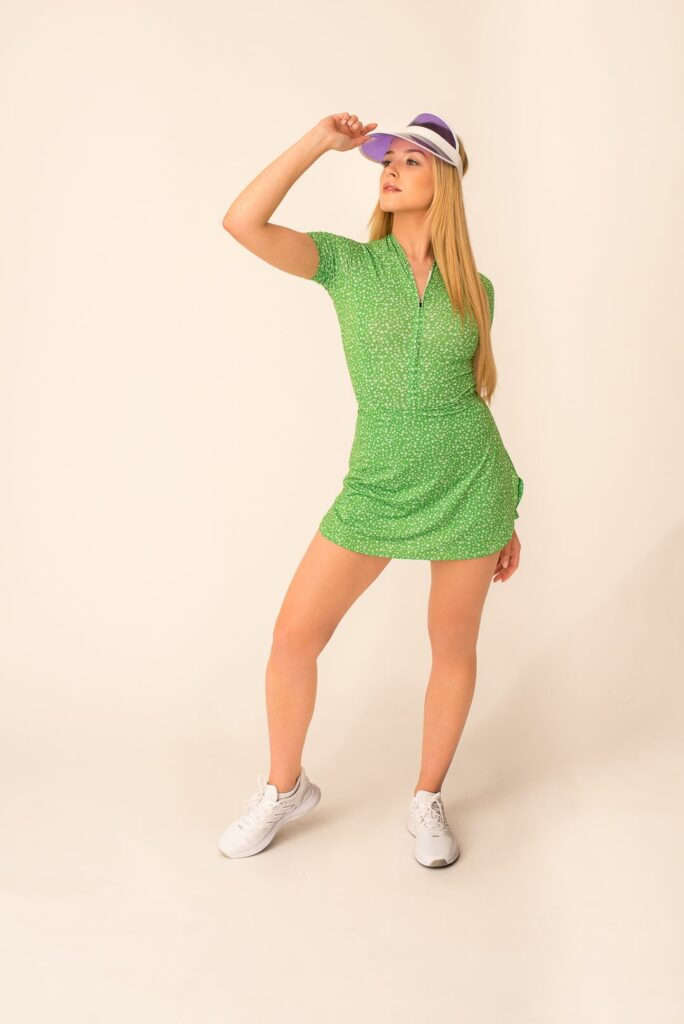 A model in a green, technical sports dress with flowers.